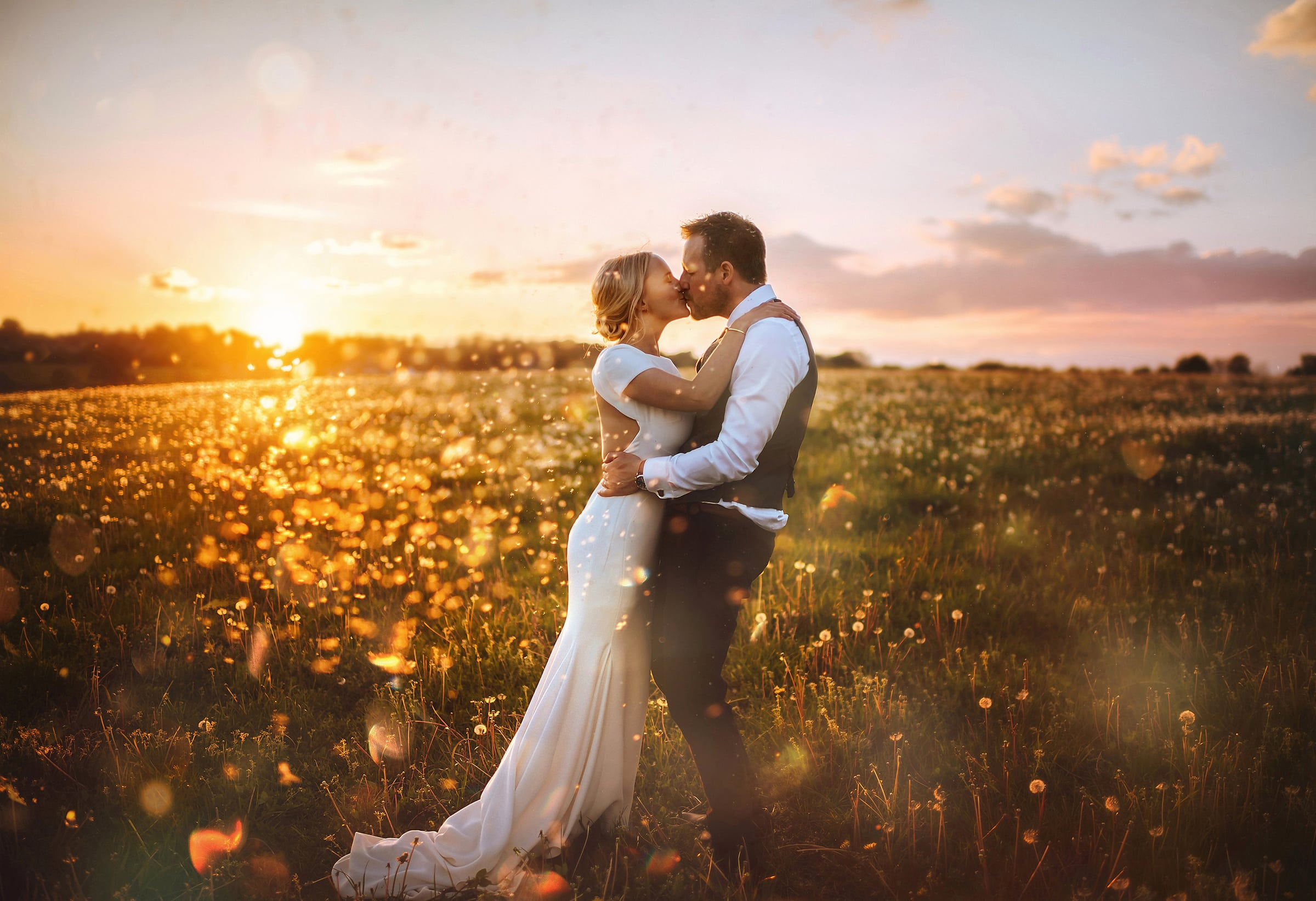 couple kissing at sunset in field